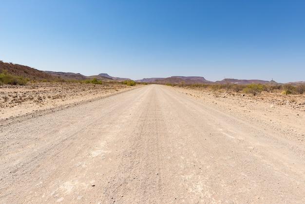 Droga szutrowa przecinająca pustynię namib, namibia, afryka