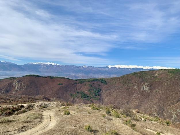 Droga w górach z niebieskim niebem i śniegiem na szczycie