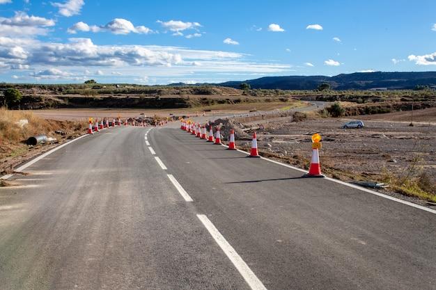 Droga w ruinie z powodu klęski żywiołowej oznaczonej stożkami zapobiegawczymi. droga w budowie. klęska żywiołowa.