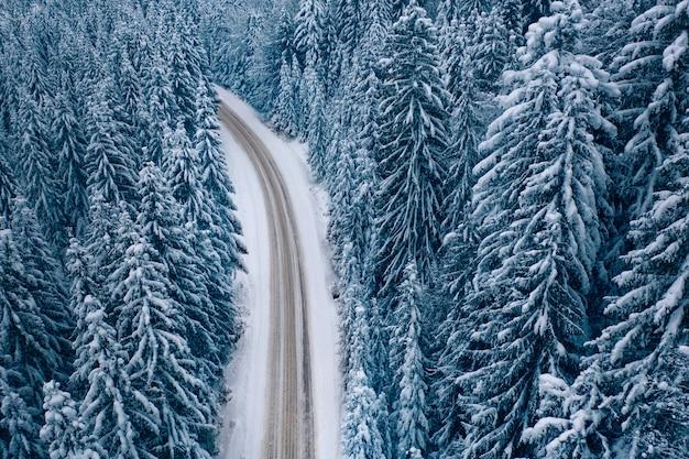 Droga w zimowym lesie górskim. widok z drona.