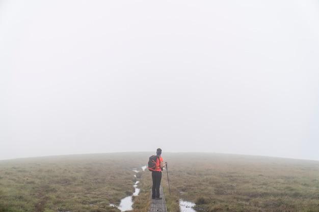 Droga wicklow w pobliżu roundwood w dzień z mgłą z wycieczkowiczem po drewnianej ścieżce.