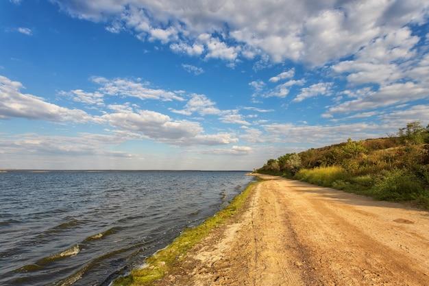 Droga wzdłuż brzegu jeziora, rzeki, na tle błękitnego nieba z chmurami belvmi