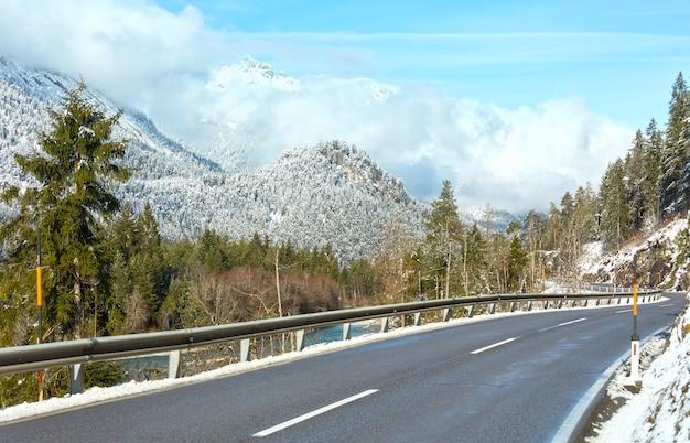 Droga wzdłuż rzeki i ośnieżonych zboczy górskich (austria, tyrol).