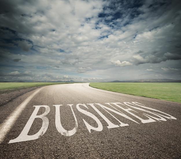 Droga z pisemnym biznesem na asfalcie. koncepcja drogi do sukcesu