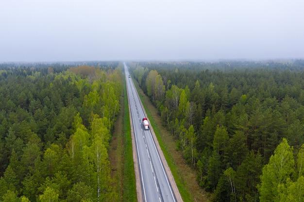 Droga z samochodami w lesie między zielonymi drzewami, widok z lotu ptaka od trutnia