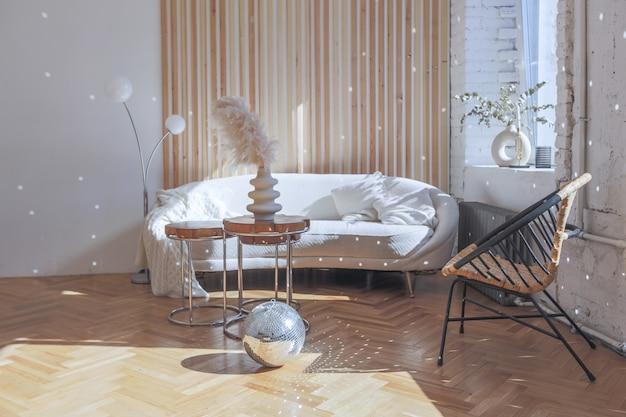 Drogi nowoczesny lekki luksusowy wystrój przestronnego salonu z drewnianymi elementami i białymi ścianami. wypełniony oryginalnymi i nietypowymi przedmiotami dekoracyjnymi