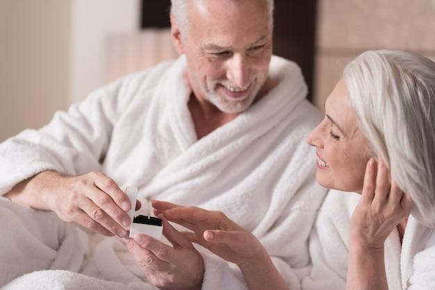 Drogi prezent. przyjemny uśmiechnięty starszy mężczyzna leżący na łóżku i dając pierścionek swojej żonie, wyrażając jednocześnie szczęście