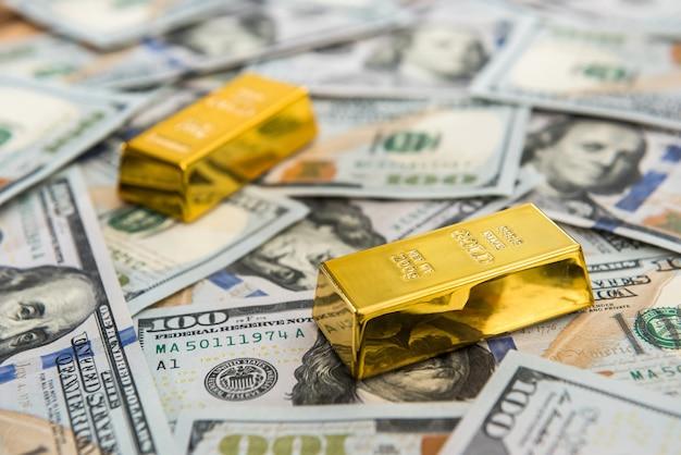 Drogi sztabka złota leżąca na dolarowych banknotach pozwala zaoszczędzić pieniądze