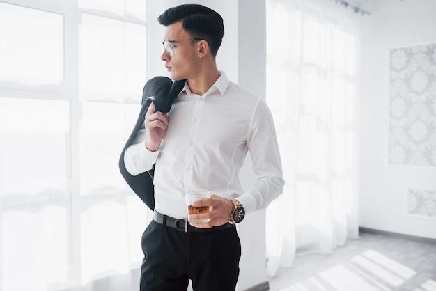 Drogie ubrania. luksusowo wyglądający mężczyzna w klasycznym stroju stoi w pokoju i trzyma górę garnituru i szklankę z alkoholem.