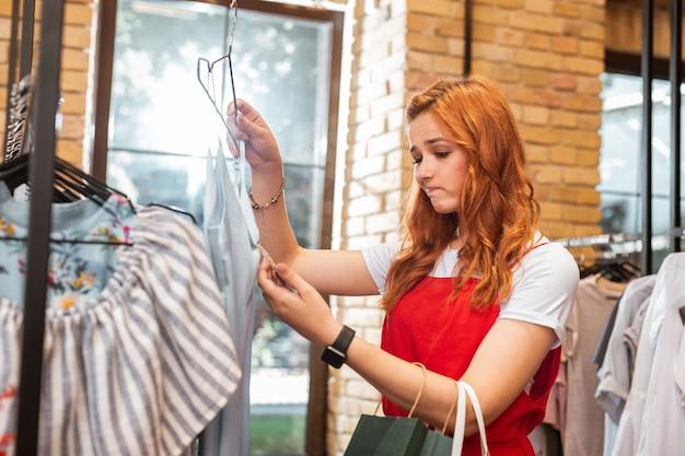 Drogie ubranie. smutna młoda dziewczyna marszczy brwi i patrzy na wysoką cenę, wybierając sukienkę w sklepie z ubraniami