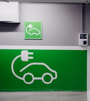 Drogowskaz bezpłatnej stacji ładowania samochodów elektrycznych na europejskim parkingu supermarketu