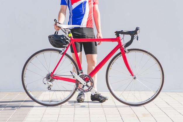 Drogowy czerwony rower i cyklista w bicyklu odziewamy na białej ścianie