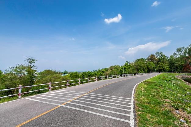 Drogowy widoku rezerwuaru zieleni drzewa i niebieskiego nieba tło.