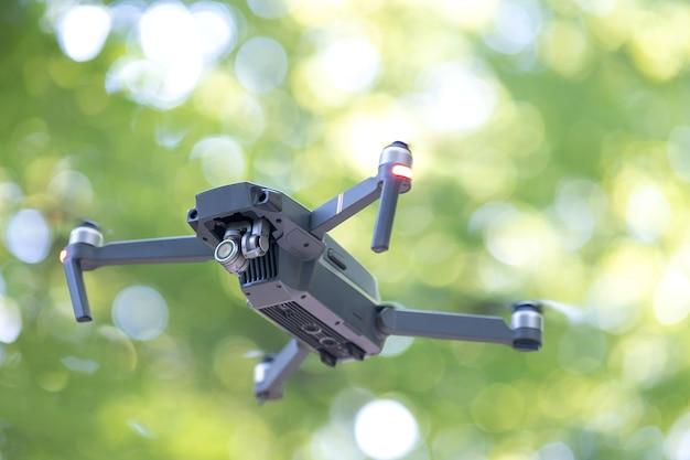 Dron helikopter z niewyraźnymi śmigłami i kamerą wideo latającą w powietrzu