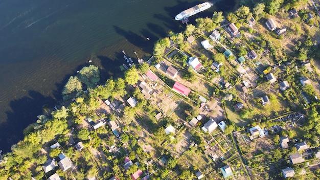 Dron przelatuje nad falującą rzeką koloru niebieskiego otoczoną lokalną wioską z różnymi budynkami i mokradłami