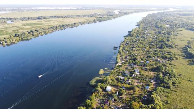 Dron przelatuje nad falującą rzeką koloru niebieskiego otoczoną lokalną wioską z różnymi budynkami oraz mokradłami i bagnami