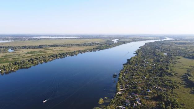 Dron przelatuje nad falującą rzeką koloru niebieskiego otoczoną lokalną wioską z różnymi budynkami