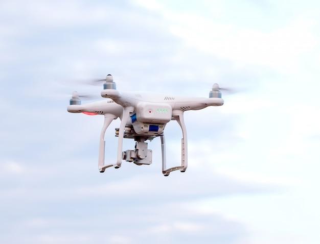 Dron quadcopter z kamerą na tle błękitnego nieba