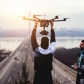 Dron zabiera ziemię. mężczyzna trzyma drona.