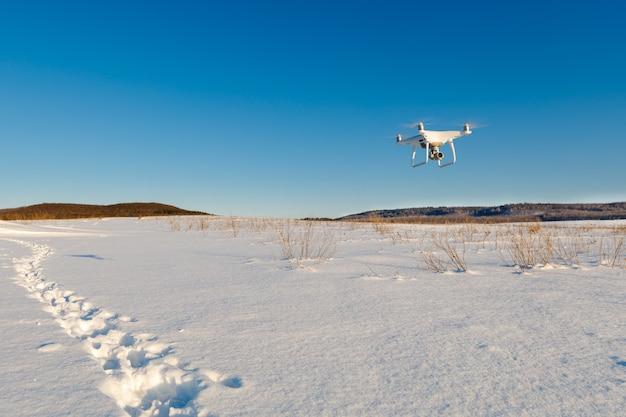 Drone lecący nad polem pokryte śniegiem w słoneczny zimowy dzień