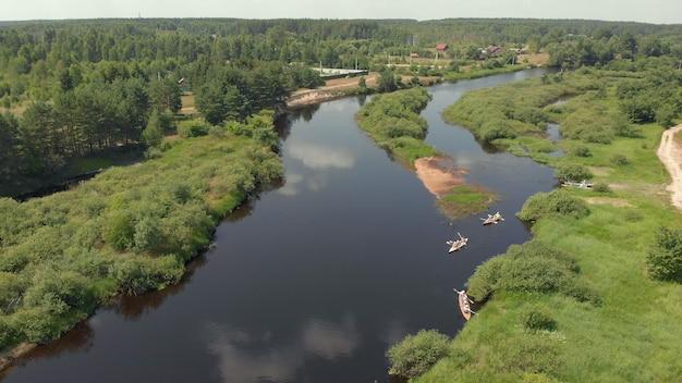 Drone punktu widzenia grupy ludzi kajakarz unoszący się na wodzie. widok z lotu ptaka z grupy kajaków w jeziorze. kajakarstwo i spływy kajakowe wzdłuż koryta rzeki z lotu ptaka. flisactwo. śledzenie łodzi