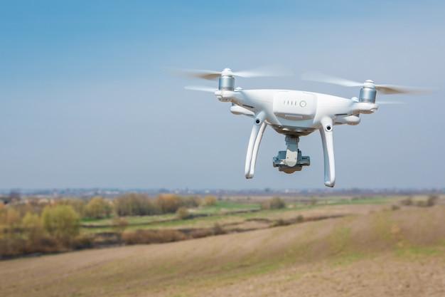 Drone quad śmigłowcem na zielonym polu