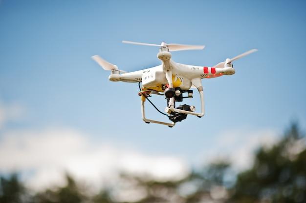 Drone quad śmigłowcem z wysokiej rozdzielczości aparat cyfrowy latający na niebieskim niebie