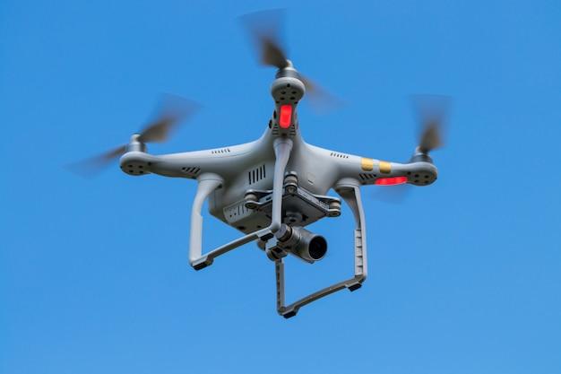 Drone quadcopter z aparatem cyfrowym na niebie