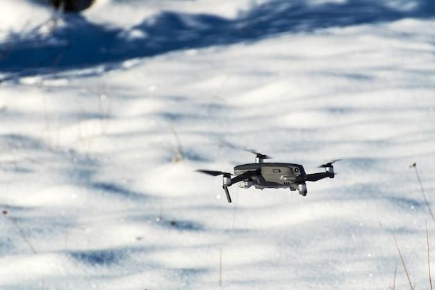 Drone quadcopter z aparatem cyfrowym. zima w tle.
