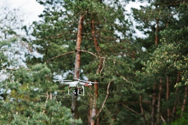 Drone quadter helikopter z cyfrowym aparatem wysokiej rozdzielczości na tle lasu sosnowego.
