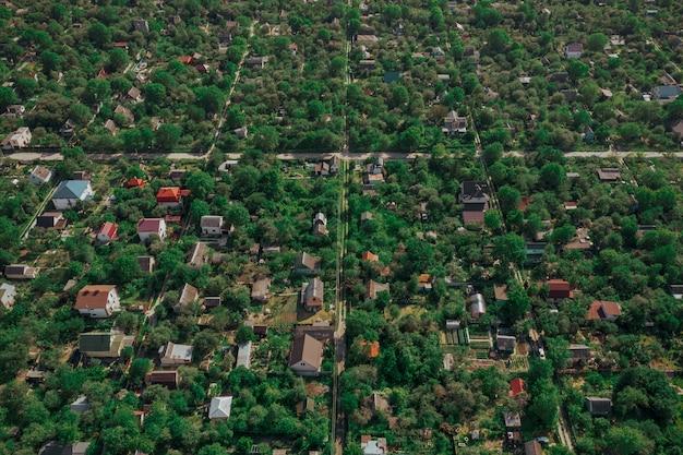 Dronowy obraz zielonych letnich ogrodów z prywatnymi inwestycjami mieszkaniowymi.