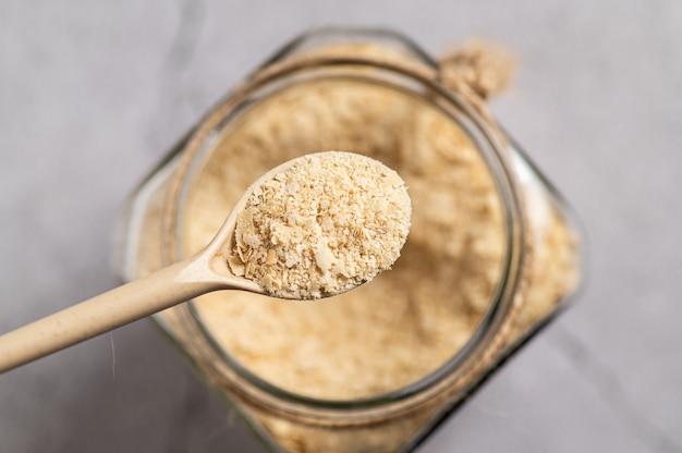 Drożdże odżywcze w płatkach z drewnianą łyżką i szklanym słojem na szarym tle