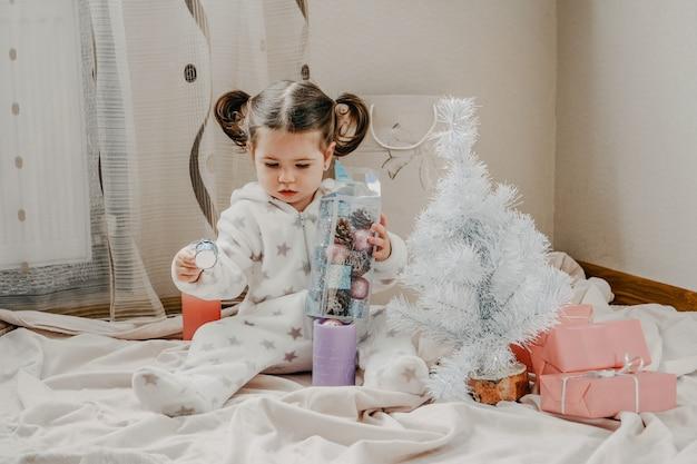 Drugi dzień świąt mała dziewczynka rozpakowuje różowe pudełka na prezenty w pobliżu choinki