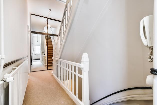 Drugie piętro domu mieszkalnego ze schodami i białym płotem na tle lustrzanych suwaków szafy