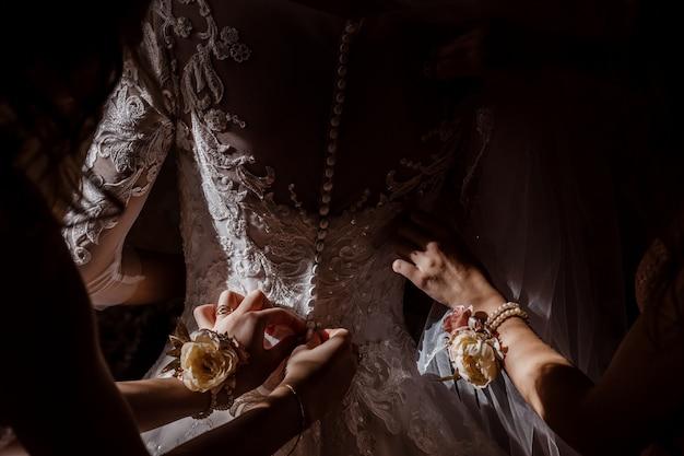 Druhna pomaga pannie młodej zapiąć gorset i dostaje sukienkę, przygotowując pannę młodą rano na dzień ślubu.