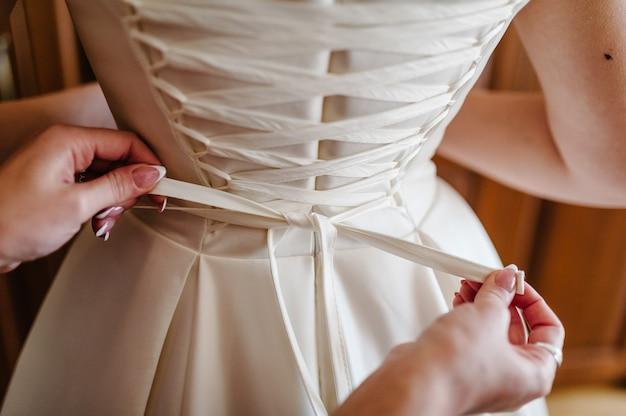 Druhna pomaga pannie młodej zapiąć gorset i założyć sukienkę, przygotowując pannę młodą rano do ślubu.