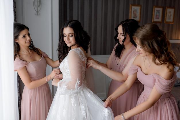 Druhny ubrane w różowe sukienki pomagają pannie młodej przygotować się do ślubu