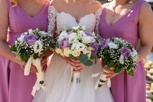 Druhny w różowych sukienkach i panna młoda trzymają bukiety. zbliżenie.