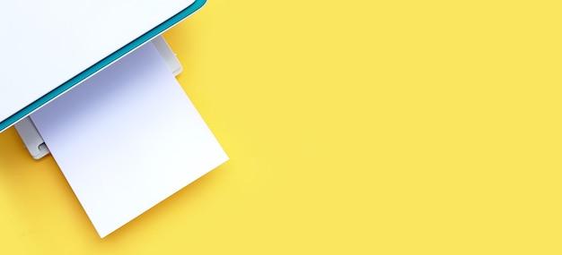 Drukarka i papier na żółtym tle. kopiuj przestrzeń