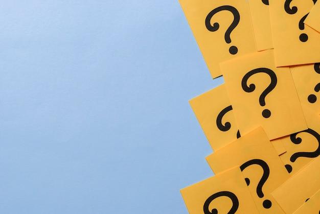 Drukowane znaki zapytania na żółtym papierze lub karcie
