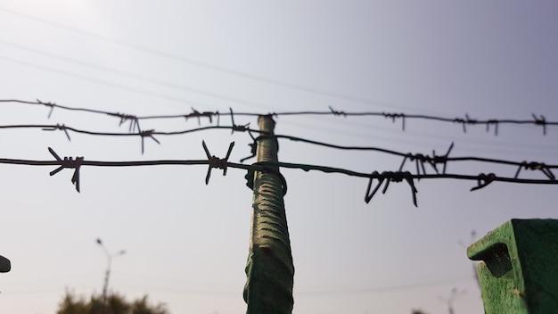 Drut kolczasty. drut kolczasty na ogrodzeniu z błękitnym niebem, aby czuć się niepokojąco. sylwetka starego ogrodzenia z drutu kolczastego i niebo o zmierzchu.