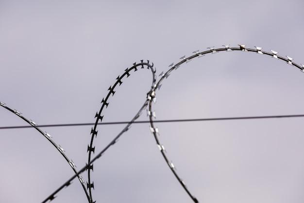 Drut kolczasty na nieba tle. drut metalowy. selektywna ostrość