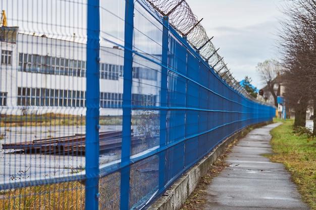 Drut kolczasty na niebieskim ogrodzeniu ograniczonego obszaru
