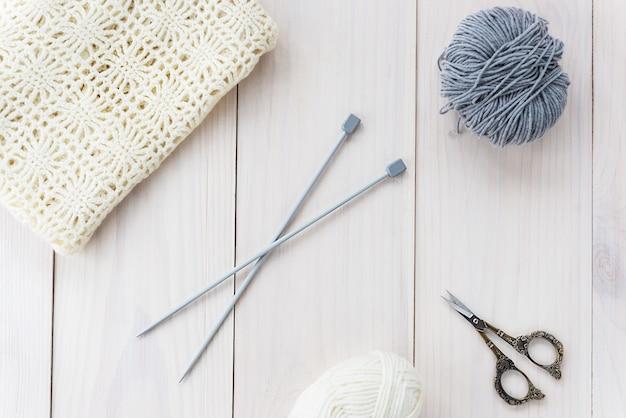 Druty motek tkaniny nici i nożyczki na drewnianym stole