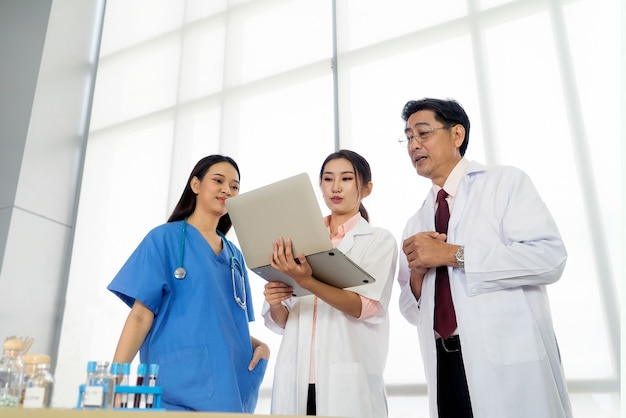 Drużyna azjatyckich lekarzy stojących razem i używać laptopa do rozmowy i dyskutować