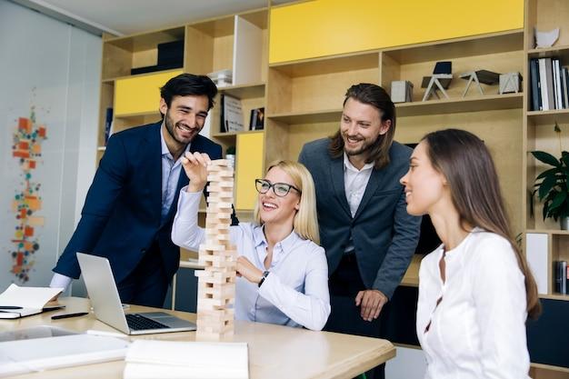 Drużyna młodzi ludzie biznesu buduje drewnianą budowę