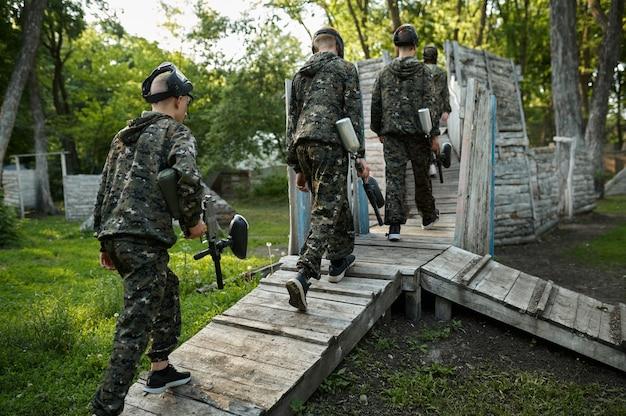 Drużyna paintballowa strzela z broni palnej, gra wojskowa