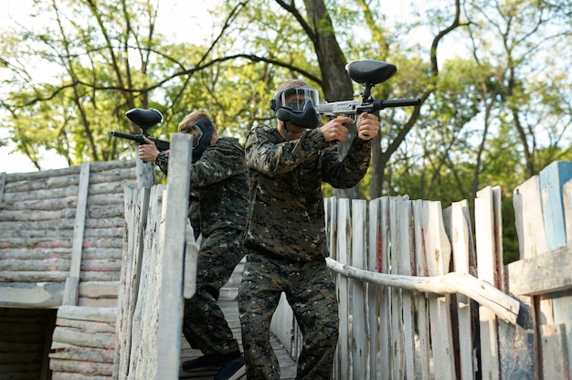 Drużyna paintballowa strzela z broni palnej, wojownicy w kamuflażach na placu zabaw w lesie. sporty ekstremalne z bronią pneumatyczną i pociskami lub markerami malarskimi, aktywna gra wojskowa w plenerze, taktyka walki
