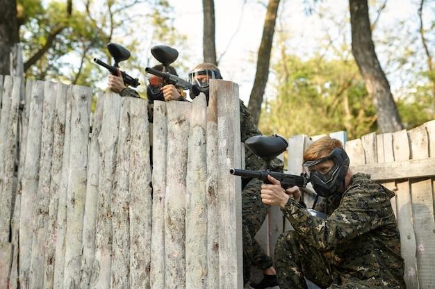 Drużyna paintballowa strzela z broni palnej, wojownicy w kamuflażach na placu zabaw w lesie