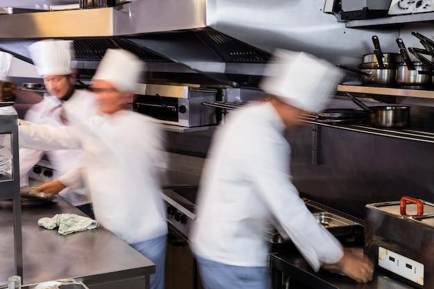 Drużyna szefów kuchni przygotowywa jedzenie w kuchni